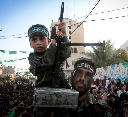 A Palestinian man carries his son during a graduation ceremony as part of a military-style summer camp organised by the Ezzedine al-Qassam brigades, the armed wing of the Hamas movement, on August 5, 2015, in Khan Yunis, in the southern Gaza Strip. The military wing of Hamas opened its Gaza summer camp on July 25 aimed at providing basic combat training for 25,000 Palestinians in the Gaza strip. Photo by Abed Rahim Khatib/ Flash90 *** Local Caption *** ???? ??? ??? ??? ??? ????? ????? ??? ??? ???? ??????