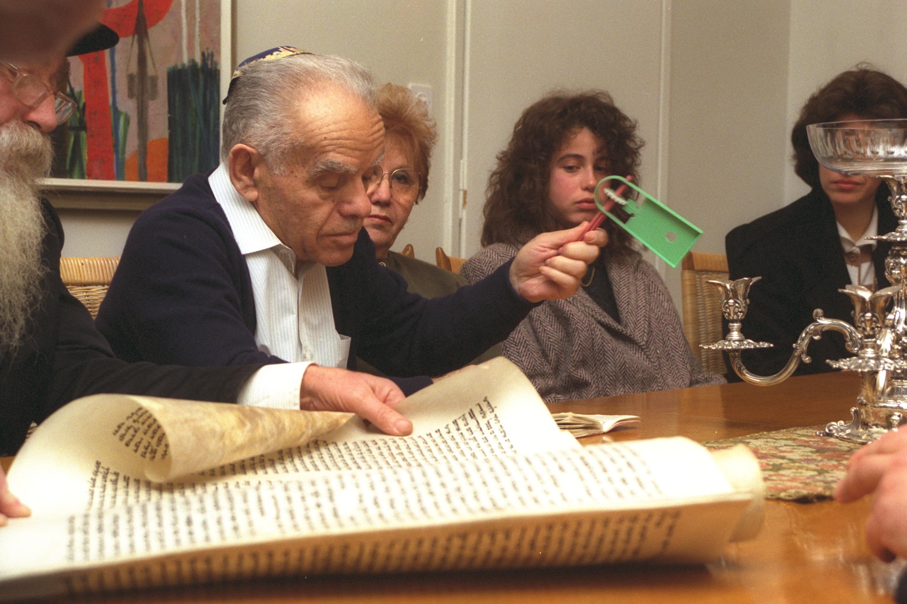 """P.M. YITZHAK SHAMIR WAVING A NOISEMAKER AT THE SOUND OF HAMAN'S NAME DURING A MEGILLA READING AT HIS HOME IN JERUSALEM ON PURIM. øàù äîîùìä éöç÷ ùîéø îøòéù áøòùï áòú ä÷øàú îâéìú àñúø, ááéú øä""""î áéøåùìéí."""